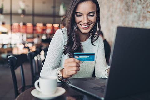 Lady sitting at coffee shop with computer and banking card
